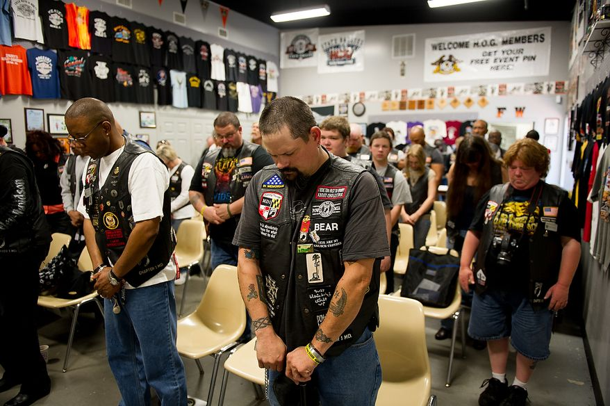 Steve Betts of Waldorf, Md., center, and other members of the Rolling Thunder's Maryland chapter pauses for a moment of silence before starting a general membership meeting to plan for their Memorial Day events at Harley Davidson's Ft. Washington store, Ft. Washington, Md., Saturday, May 12, 2012. (Andrew Harnik/The Washington Times)