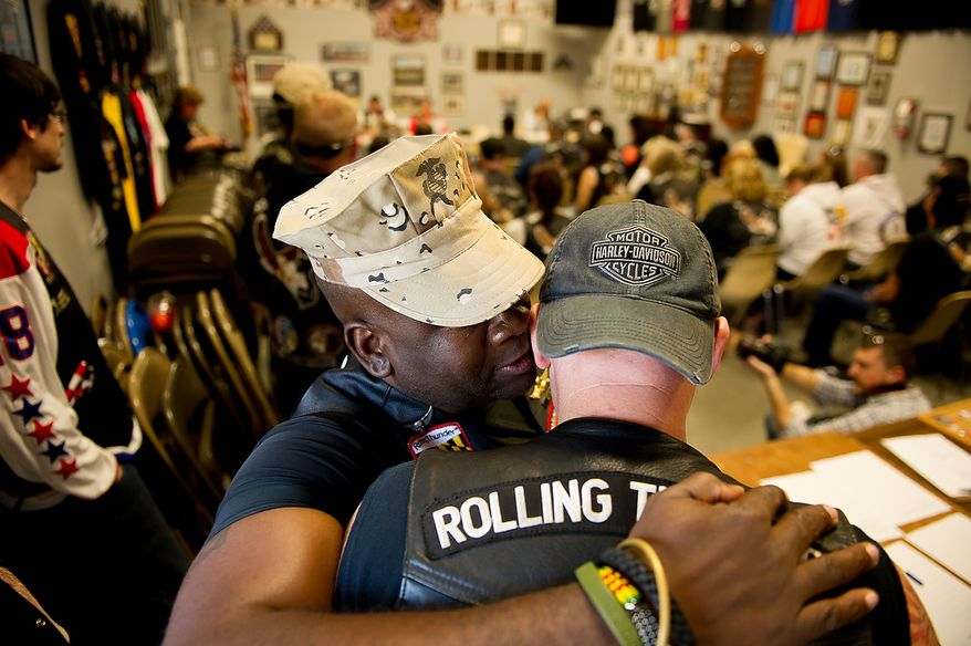 Marine Cpl. Joe Coaxum, left, whispers with Air Force Chief Master Sgt. Daryl Web, right, as Rolling Thunder's Maryland chapter holds a general membership meeting to plan for their Memorial Day events at Harley Davidson's Ft. Washington store, Ft. Washington, Md., Saturday, May 12, 2012. (Andrew Harnik/The Washington Times)