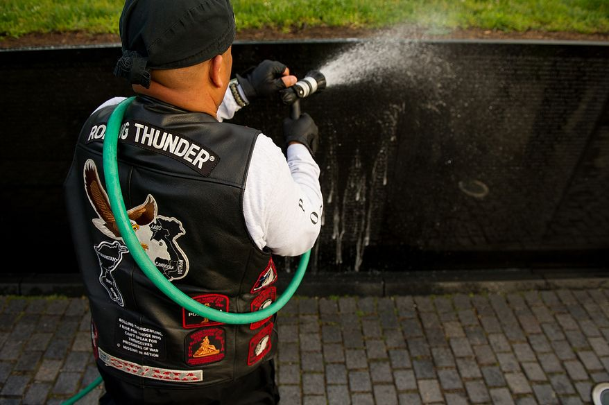 Retired Coast Guard Corpsman Quezryth Chunn of Ft. Washington, Md., hoses soap off the Vietnam Memorial as members of Rolling Thunder's Maryland chapter clean the memorial's wall in the early morning, Washington, D.C., Sunday, May 13, 2012. (Andrew Harnik/The Washington Times)