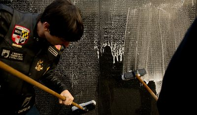 Brandon Lutzow of Waldorf, Md., left, helps scrub the Vietnam Memorial along with other members of Rolling Thunder's Maryland chapter as they clean the memorial's wall in the early morning, Washington, D.C., Sunday, May 13, 2012. (Andrew Harnik/The Washington Times)