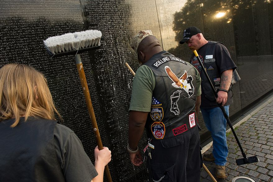 Deborah Shekleton of Waldorf, Md., 17, Marine Cpl. Joe Coaxum, and Debora's father Jim read some of the names on the wall while waiting for another member of the Rolling Thunder Maryland Chapter to hose soap off the Vietnam Memorial while cleaning the memorial's wall in the early morning, Washington, D.C., Sunday, May 13, 2012. (Andrew Harnik/The Washington Times)