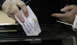 "An Egyptian woman casts her ballot in the country's presidential election on Wednesday, May 23, 2012, in the Zamalek neighborhood of Cairo, Egypt. The ballot, in Arabic, reads, ""the Arab Republic of Egypt polling station for the presidency."" (AP Photo/Maya Alleruzzo)"
