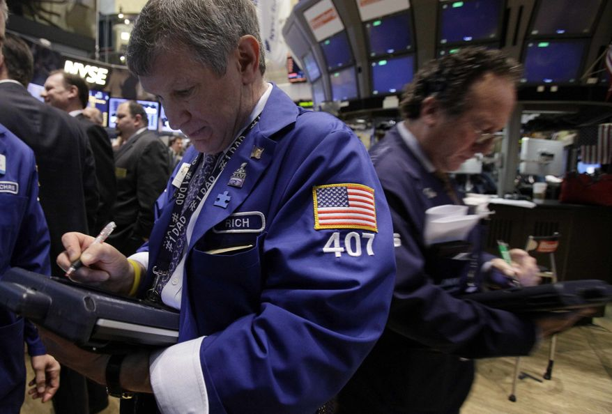 In an April 16, 2012, photo trader Richard Newman, left, works on the floor of the New York Stock Exchange. Wall Street headed for another day of losses, Wednesday May 23, 2012, with Dow Jones industrial futures down 0.5 percent to 12,410 and S&P 500 futures 0.6 percent lower at 1,306.50. (AP Photo/Richard Drew)