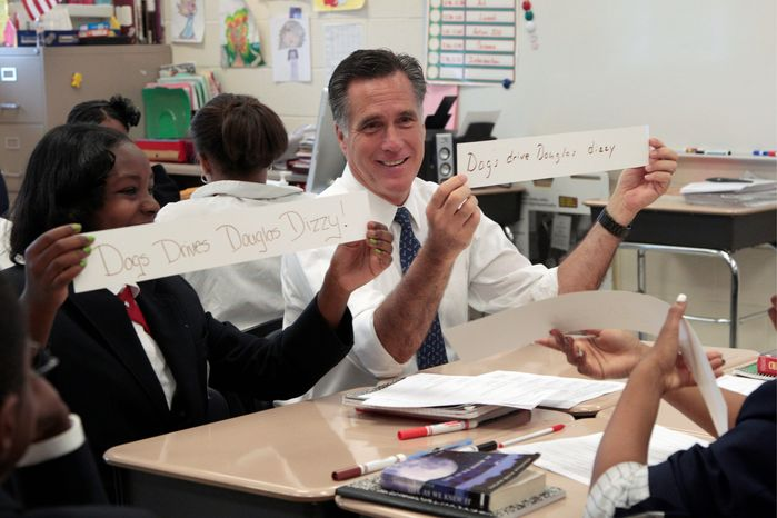 """Republican presidential candidate Mitt Romney and Salina Beattie display work they did together in a sixth grade language arts class during Mr. Romney's visit to Universal Bluford Charter School in West Philadelphia, Pa. His statement that """"just getting smaller classrooms didn't seem to be the key"""" to improving education was challenged. (Associated Press)"""