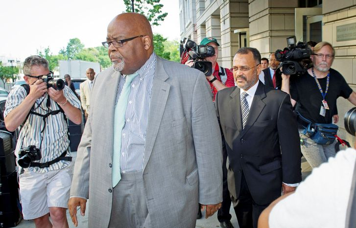 Howard L. Brooks (right), an aide to D.C. Mayor Vincent C. Gray, makes his way to a waiting car after pleading guilty Thursday in federal court to lying about furtive campaign payments to candidate Sulaimon Brown before the 2010 Democratic primary for mayor. (Rod Lamkey Jr./The Washington Times)