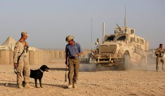 ** FILE ** Ringo, a bomb-sniffing dog, listens to trainer Adam Ward, a contractor working for American K-9 Interdiction, as dog handler Marine Cpl. William Childs observes in Helmand province, Afghanistan, in 2009. The Pentagon also has spent more than $200 million a year developing devices to detect roadside bombs. (Associated Press)