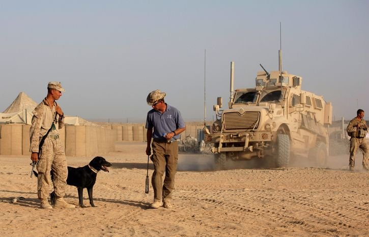 ** FILE ** Ringo, a bomb-sniffing dog, listens to trainer Adam Ward, a contractor working for American K-9 Interdiction, as dog handler Marine Cpl. William Childs observes in Helmand province, Afghanistan, in 2