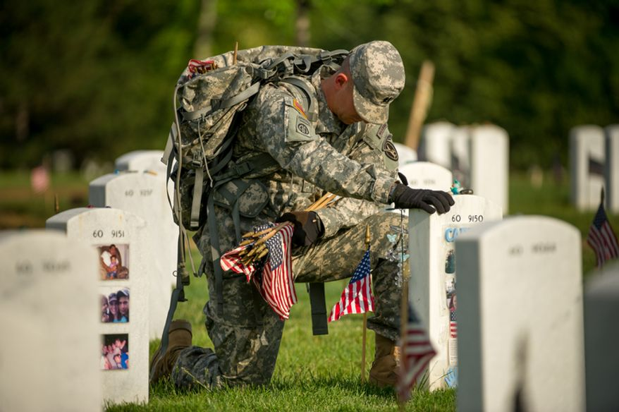 ** FILE ** Old Guard Platoon Leader Matthew Hernandez pauses to mourns his friend Sgt. 1st Class Carlos Santos-Silva in front of his grave in section 60 as Hernandez and other soldiers place small American flags at each grave at Arlington National Cemetery to honor the nation's fallen service members in Arlington, Va., Thursday, May 24, 2012. (Andrew Harnik/The Washington Times)