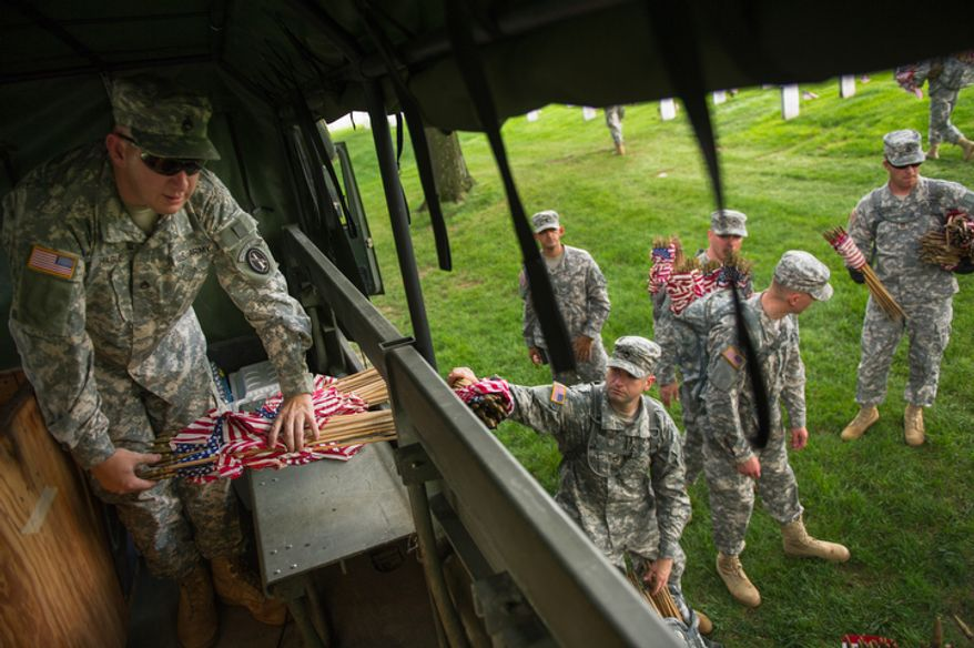 Staff Sgt. James Hague, left, hands soldiers with the Fife and Drum Core small America flags to place at each grave at Arlington National Cemetery.  (Andrew Harnik/The Washington Times)