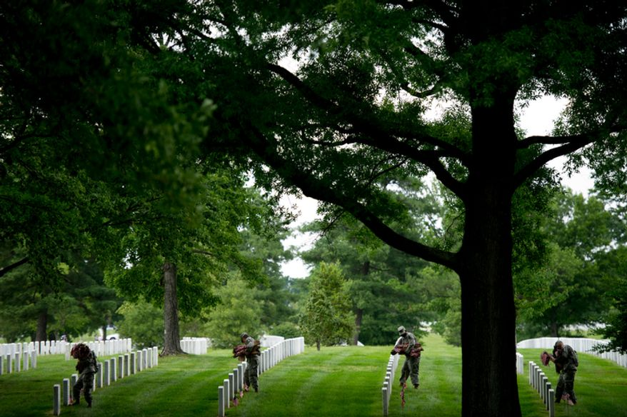 Soldiers place small America flags at each grave at Arlington National Cemetery to honor the nation's fallen armed forces.  The annual tradition has been carried out by the 3rd U.S. Infantry Regiment, The Old Guard, since 1948.  (Andrew Harnik/The Washington Times)