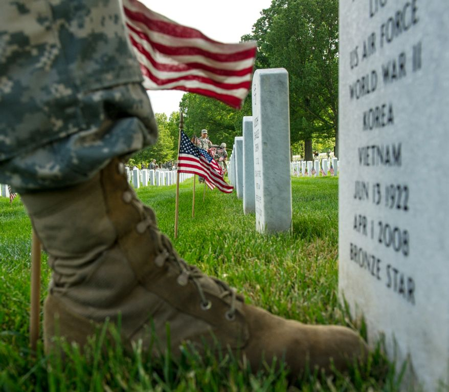 A soldiers boot as he places a small America flags at a grave at Arlington National Cemetery. (Andrew Harnik/The Washington Times)
