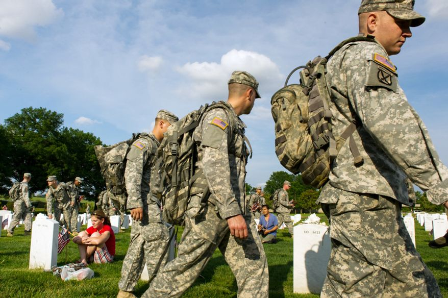 Honor Guard soldiers place American flags at each grave at Arlington National Cemetery to honor the nation's fallen service members as Air Force Maj. Terry Dutcher (left), based at Hill Air Force Base in Utah, cries at the grave of her son, Army Cpl. Michael Avery Pursel, 19, who was killed in Iraq in 2007, Arlington, Va., Thursday, May 24, 2012. (Andrew Harnik/The Washington Times)