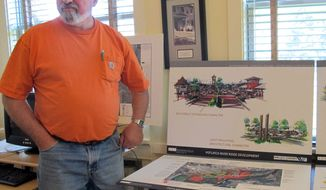 Potlatch, Idaho, Mayor David Brown stands in front of conceptual drawings of plans to revive the town. (AP Photo/Nicholas K. Geranios)