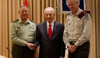 **FILE** Gen. Chen Bingde (left), chief of the General Staff of the Chinese People's Liberation Army, Israeli President Shimon Peres (center) and Lt. Gen. Benny Gantz, Israel military chief, pose for the media during a meeting at Peres' residence in Jerusalem. (Associated Press)