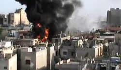 This image made from amateur video released by the Shaam News Network and accessed on Wednesday, May 23, 2012, purports to show a building on fire from shelling in Homs province of Syria. (AP Photo/Shaam News Network via AP video)
