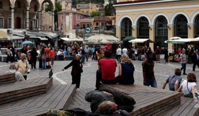 ** FILE ** A man sleeps at Monastiraki Square in central Athens in May, 2012. Homelessness, the most visible sign of Greece's financial despair, has risen by around 25 percent, according to estimates by a state-funded relief agency. (Associated Press)