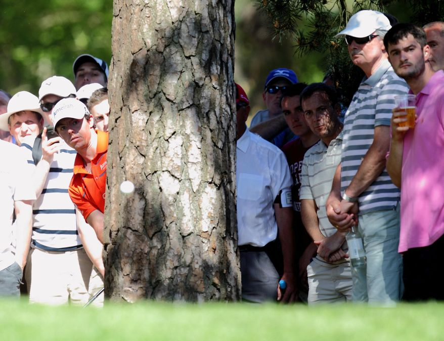 Rory McIlroy looks out from behind a tree to follow the flight of his ball during Day 2 of the BMW PGA Championship at Wentworth Golf Club, in Wentworth, England, on Friday May 25, 2012. (AP Photo / Steve Parsons, PA)