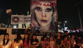 Members of a religious group stand in front of a picture of pop star Lady Gaga as they hold a protest against her concert near the venue in suburban Pasay, south of Manila, Philippines, on Monday May 21, 2012. (AP Photo/Aaron Favila)