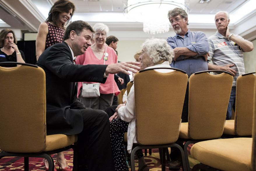 Former senator and governor George Allen, seated at left, talks with Dr. Paulette Maggiolo, of Woodstock, Va., after the final debate with his three rivals before the June 12th Virginia republican primary, at the Fairview Park Marriott in Falls Church, Va., on May 25, 2012. Recent polls give Allen a comfortable lead among likely voters in the primary, which will determine the challenger to former governor Timothy M. Kaine, who is unopposed in the democratic primary. (T.J. Kirkpatrick/Special to The Washington Times)
