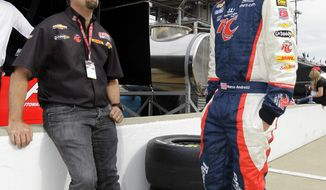 Owner Michael Andretti, left, talks with his son and driver Marco Andretti during practice for IndyCar's Indianapolis 500 race at Indianapolis Motor Speedway in Indianapolis on Saturday, May 12, 2012. (AP Photo/Darron Cummings)