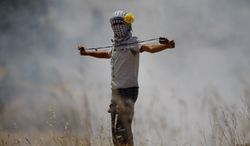 A Palestinian demonstrator prepares to hurl a stone toward Israeli troops during a protest May 25, 2012, against the expansion of the nearby Jewish settlement of Halamish in the West Bank village of Nabi Saleh, near Ramallah. (Associated Press)