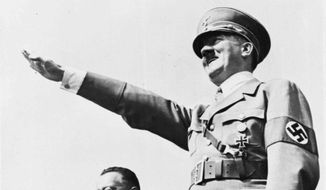 **FILE** German Chancellor Adolf Hitler (right) salutes a huge crowd July 31, 1938, at a sports meeting in Breslau, Germany. (Associated Press)