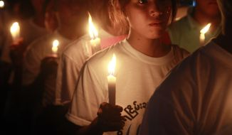 Protesters hold candles during a candlelight vigil in Yangon, Myanmar Friday, May 25, 2012. (AP Photo/Khin Maung Win)