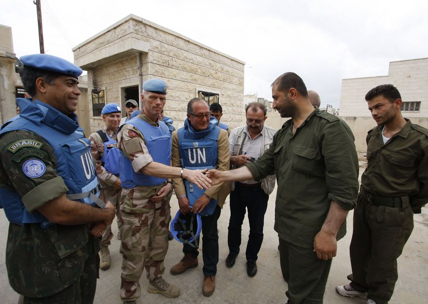 ** FILE ** In this picture taken during a U.N. observer-organized tour, the head of the advance team of U.N. observers, Maj. Gen. Robert Mood, center left, shakes hands with a Syrian security officer during their visit to Hama city, central Syria, on Thursday, May 3, 2012. (AP Photo/Muzaffar Salman)
