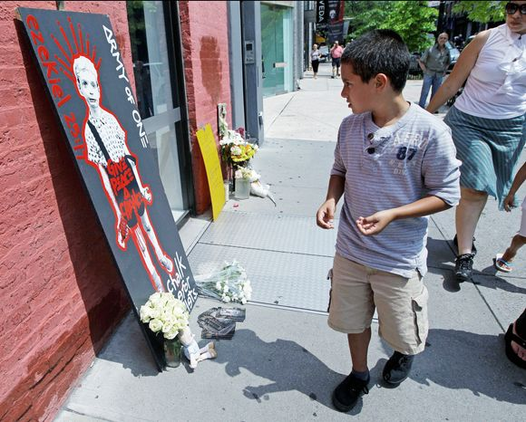 A boy stops to look at a makeshift memorial to Etan Patz in New York on Sunday. Etan was 6 when he disappeared in 1979. The memorial sprung up at the site where, according to police, suspect Pedro Hernandez claims the killing took place. (Associated Press)