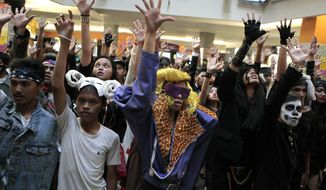 Fans of pop star Lady Gaga perform a flash mob dance at a shopping mall in Jakarta, Indonesia, on Sunday, May 27, 2012, to protest the cancellation of a sold-out show after Islamist hard-liners threatened violence. (AP Photo/Dita Alangkara)