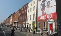 """In Dublin, a huge banner depicting Ireland's being bled dry by austerity calls for a """"no"""" vote in the referendum on the European Union's fiscal treaty. (AP Photo/Shawn Pogatchnik)"""