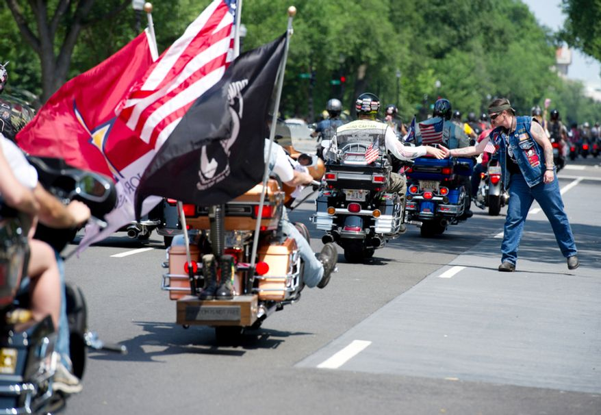 A man who identified himself only as Bobby from Kentucky high-fives passing motorcyclists as they make their way down Constitution Avenue in Washington, D.C. on Sunday, May 27, 2012 during the annual Rolling Thunder ride. (Barbara L. Salisbury/The Washington Times)