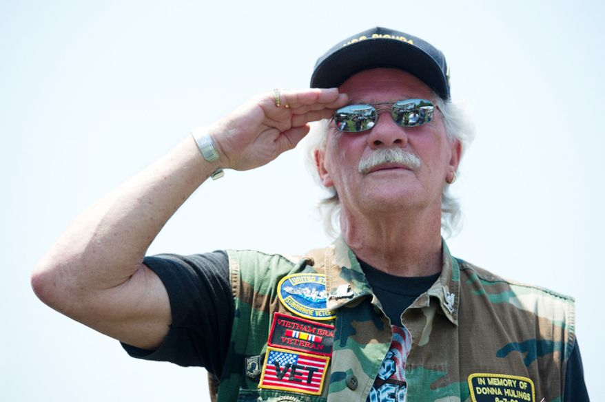 Dan Hulings, of Chambersburg, Penn., who served aboard the USS Bicuda in Key West, Fla. from 1963 to 1967, salutes during the national anthem at the Rolling Thunder stage. (Barbara L. Salisbury/The Washington Times)