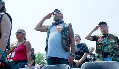 People hold their hands over their hearts and salute, including J.T. Mare, center, of Key Largo, Fla., and Dan Hulings, right, of Chambersburg, Penn., during the singing of the national anthem at the Rolling Thunder stage in Washington, D.C. (Barbara L. Salisbury/The Washington Times)