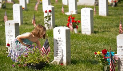 A girl places a rose at the headstone of U.S. Army Captain Ian Patrick Weikel on Memorial Day at Arlington National Cemetery. (Rod Lamkey Jr/The Washington Times)