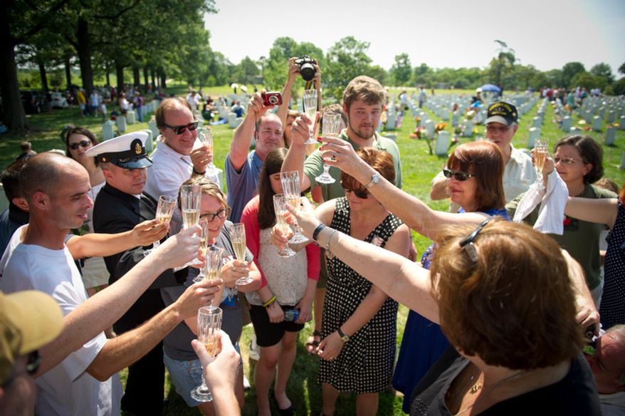 Family members raise a toast in memory of U.S. Army First Lieutenant Kenneth M. Ballard at his grave site on Memorial Day at Arlington National Cemetery. (Rod Lamkey Jr/The Washington Times)