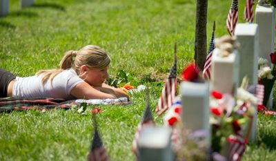 Stephanie Montgomery lays in the grass beside the grave of her brother U.S. Army Staff Sergeant Thaddeus Scott Montgomery. (Rod Lamkey Jr/The Washington Times)