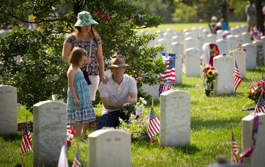 A family who did wish to give their names kneel before a headstone on Memorial Day at Arlington National Cemetery. (Rod Lamkey Jr/The Washington Times)