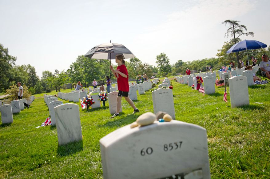 A girl walks past the rows of headstones, using an umbrella for shade on Memorial Day at Arlington National Cemetery. (Rod Lamkey Jr/The Washington Times)