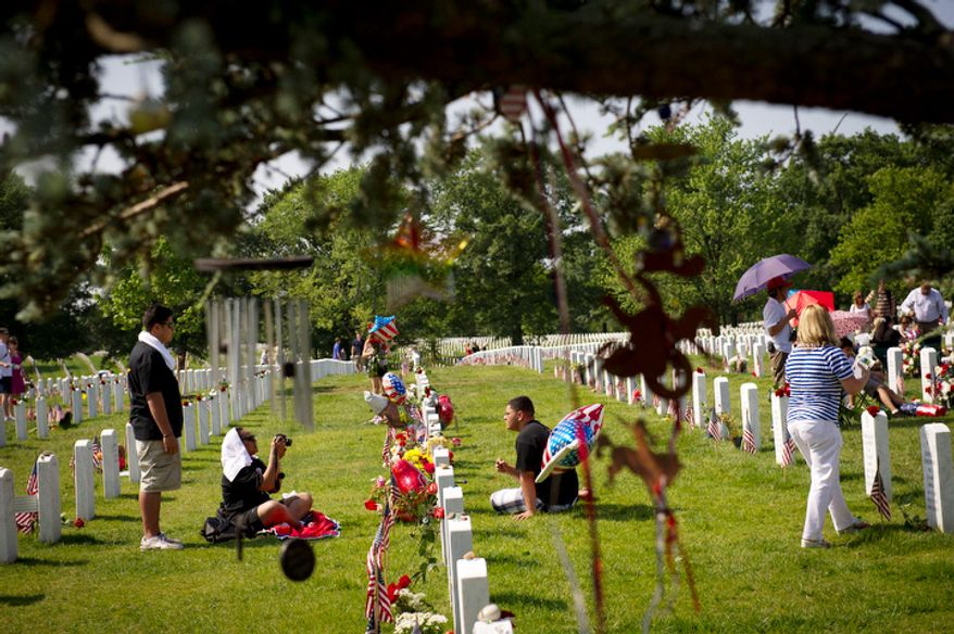 Families gather around the headstones of their loved ones on Memorial Day at Arlington National Cemetery. (Rod Lamkey Jr/The Washington Times)