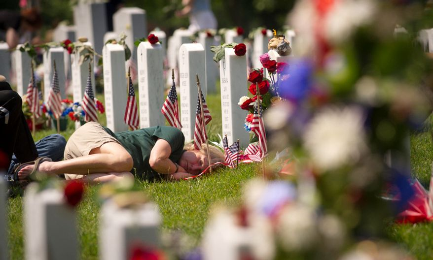 A woman rests curled up near a grave site on Memorial Day at Arlington National Cemetery. (Rod Lamkey Jr/The Washington Times)