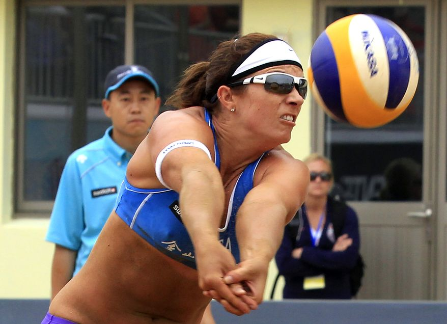 Misty May-Treanor receives the ball during the first round of the women's match with her partner Kerri Walsh in the FIVB Beach Volleyball World Tour Grand Slam in China, Wednesday, May 2, 2012. (AP Photo/Eugene Hoshiko)