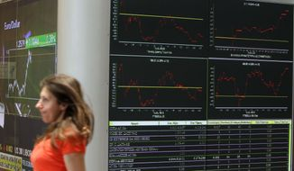 A woman walks past displays at the Stock Exchange in Athens on Friday, May 25, 2012. (AP Photo/Thanassis Stavrakis)