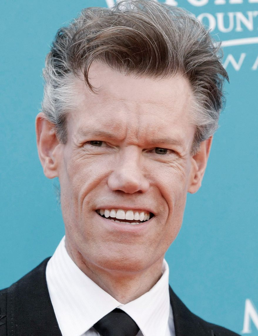 FILE - In this April 18, 2010 file photo, country singer Randy Travis arrives at the 45th Annual Academy of Country Music Awards in Las Vegas. Travis is fine and resting after passing out during a benefit concert. The 52-year-old was performing Sunday at the Crystal Heart Gala, an annual benefit for the Huguley Memorial Medical Center in Fort Worth, Texas, when he began to have trouble and passed out. (AP Photo/Dan Steinberg, file)