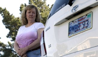 Candice Hoglan poses April 21, 2012, for a portrait with her vehicle with a license plate commemorating the events of Sept. 11, 2001, in Sunnyvale, Calif. Hoglan's nephew Mark Bingham was one of the passengers of United Airlines Flight 93, which was hijacked by terrorists on Sept. 11. (Associated Press)