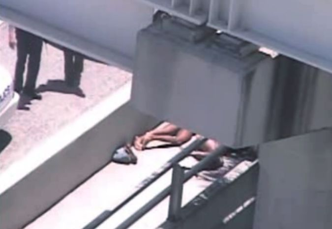 In this image taken from video, Miami police officers (left) stand watch near a naked man (second from right) who was shot dead by a police officer when he refused to stop chewing on the face of another naked man (partially obscured