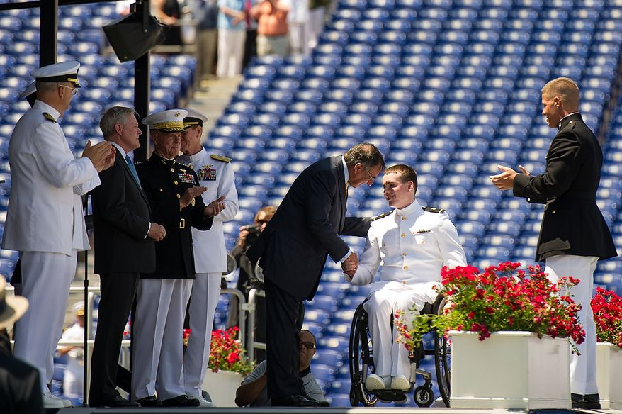 Midshipman Kevin Joseph Hillery, who was paralyzed from the waist down by a falling tree during his junior year, shakes hands with Secretary of Defense Leon E. Panetta (third from right) as he takes the stage to receive his diploma during graduation ceremonies for the U.S. Naval Academy's class of 2012 at the Navy-Marine Corps Stadium in Annapolis on Tuesday, May 29, 2012. (Andrew Harnik/The Washington Times)