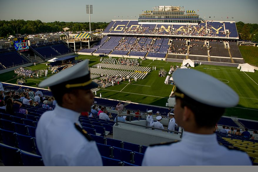 Midshipmen Plebes Langston Williams, left, and Nickos Leondaridis-Mena, right, stand on the upper level of the stadium before graduation is held for the U.S. Navy Academy's class of 2012 at the Navy-Marine Corps Stadium, Annapolis, Md., Tuesday, May 29, 2012. (Andrew Harnik/The Washington Times)