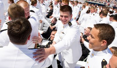 Graduates Steve Dukleth of Glen Ellyn, Ill., left, and Devereux Smith of McLean, Va., center, congratulate each other as the U.S. Naval Academy's class of 2012 take their oath during their graduation ceremony at the Navy-Marine Corps Stadium, Annapolis, Md., Tuesday, May 29, 2012. (Andrew Harnik/The Washington Times)
