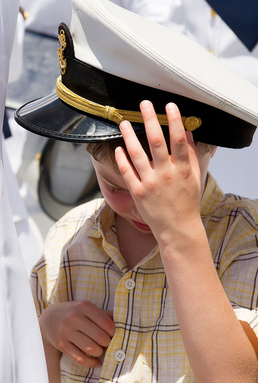Robert Martinaggi, 7, of Severn, Md., puts on a tossed hat following the U.S. Naval Academy's class of 2012 hat toss at the end of their graduation at the Navy-Marine Corps Stadium, Annapolis, Md., Tuesday, May 29, 2012. (Andrew Harnik/The Washington Times)